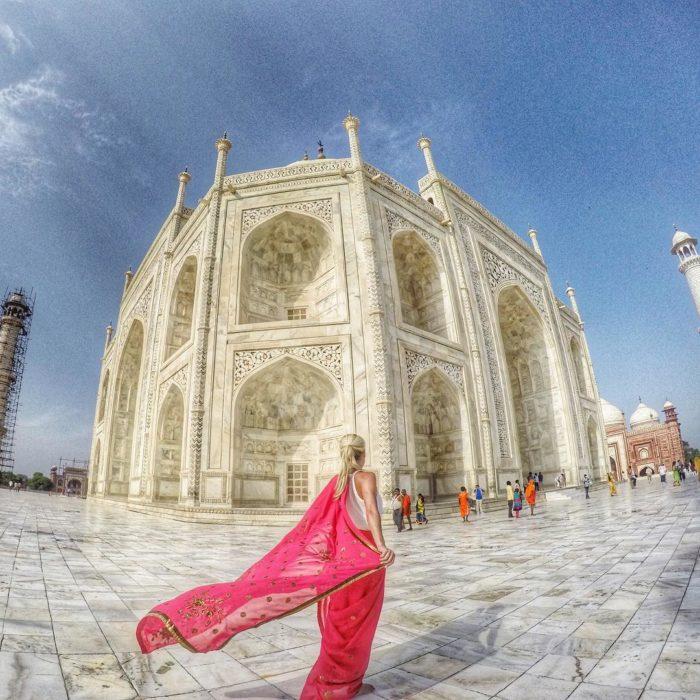 mujer de espaldas frente a un edificio en la India