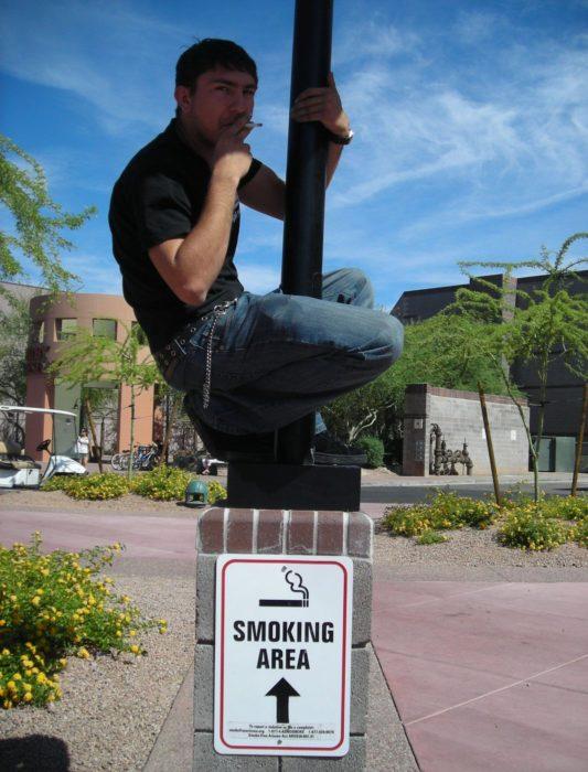 hombre fumando en un poste