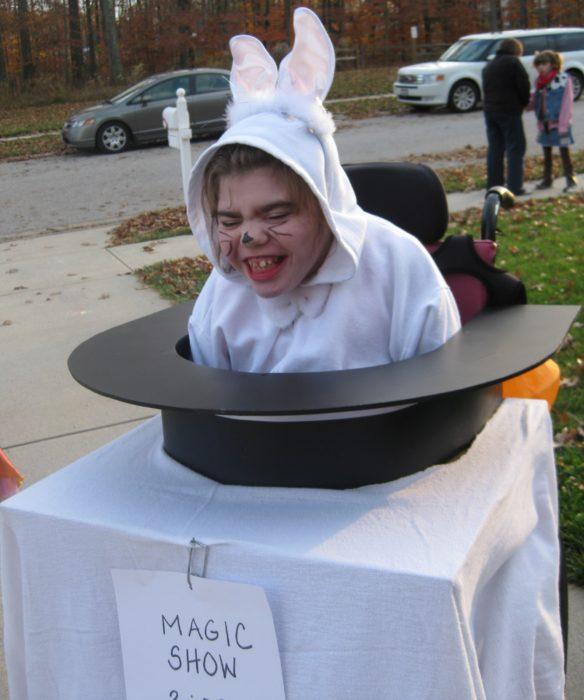 persona en silla de ruedas disfrazada de conejo dentro del sombrero