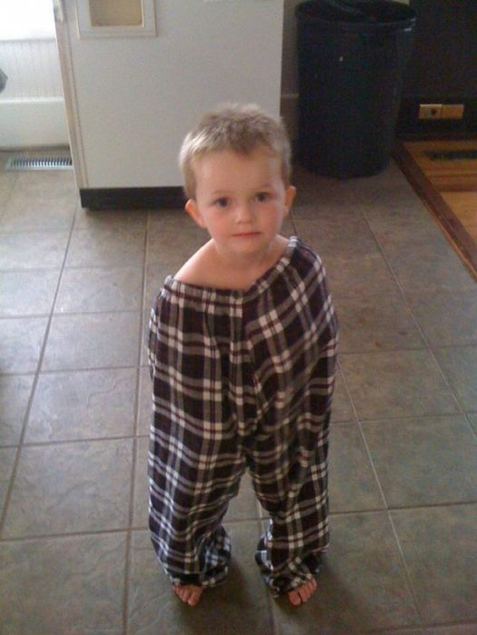 niño cubierto en pantalones gigantes