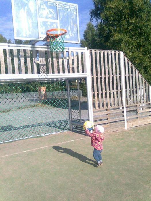 niño pequeño sosteniendo pelota que tirará hacia un aro de basquetbol muy alto