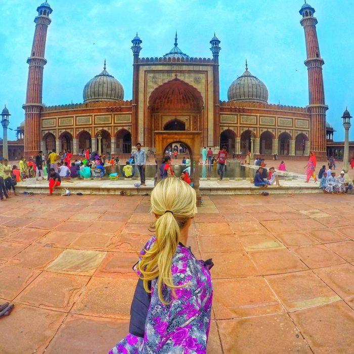 mujer frente a un hermoso edificio de la india