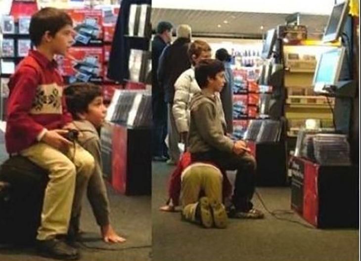 niños se sientan encima el uno del otro para jugar videojuegos