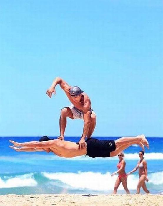hombre parece que surfea en los aires tomando como tabla a otro hombre