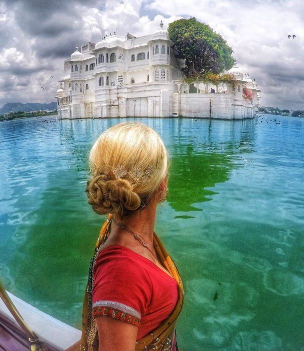 mujer de espaldas a cámara frente a lago