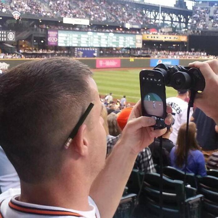 hombre con celular mirando partido deportivo