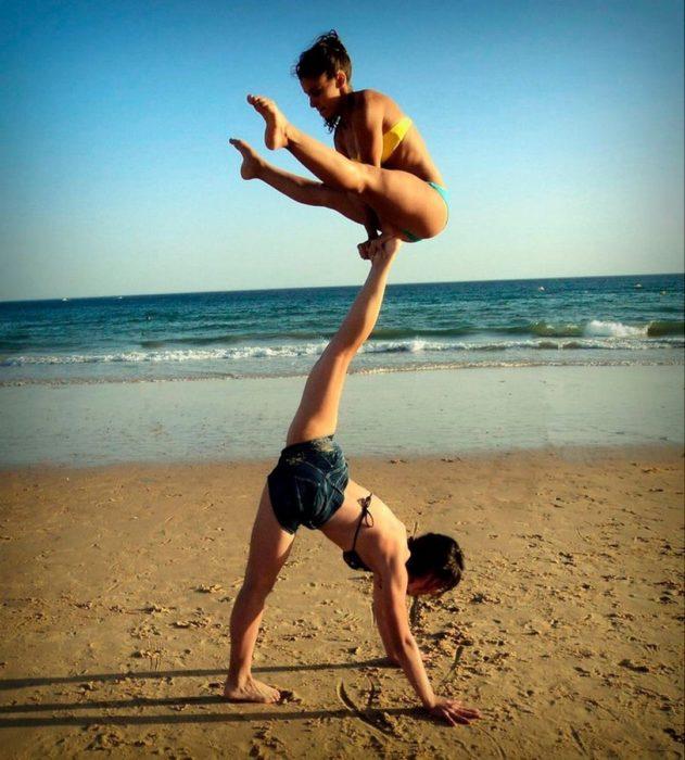 dos mujeres haciendo posición complicada de yoga