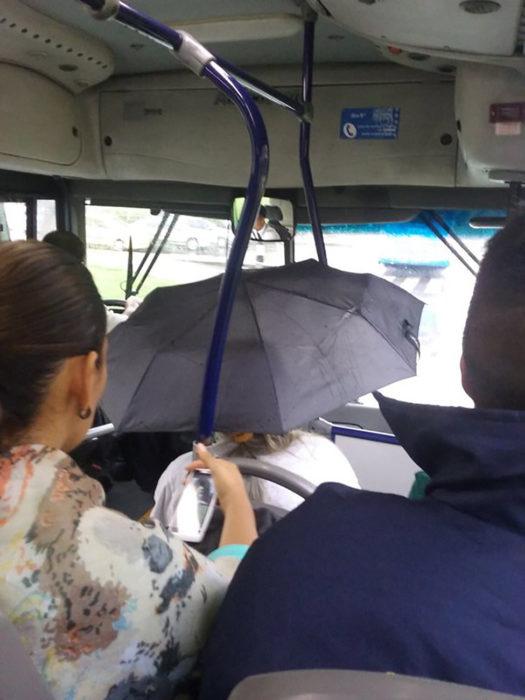 señora con paraguas dentro del autobús