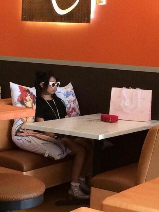 chica con dos almohadas en un café