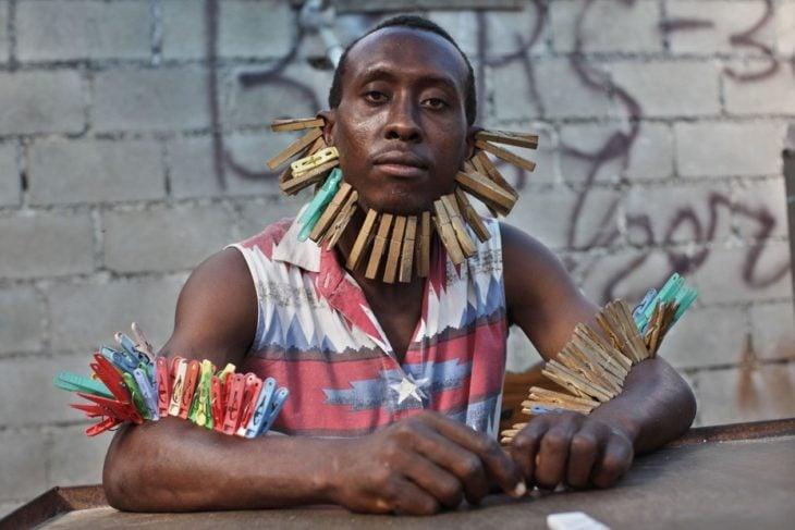 hombre con pinzas para ropa en los brazos y el mentón