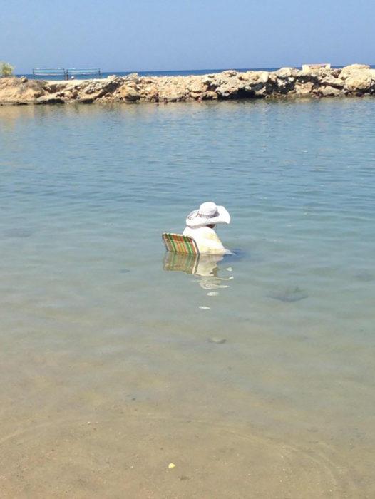 señora sentada en medio del mar