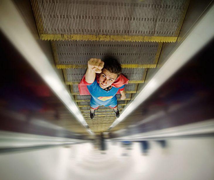 chico en escaleras eléctricas vestido de superman juega con la perspectiva