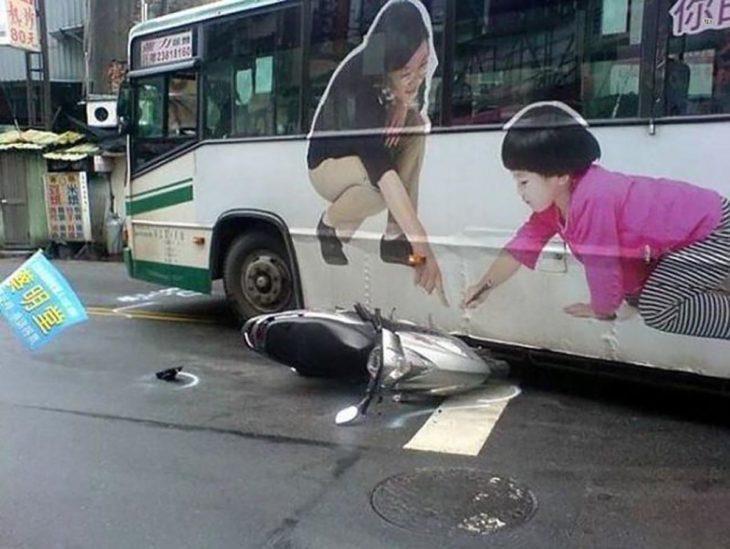 moto estrellada contra autobuz que tiene de publicidad a una señora y un niño señalando el piso