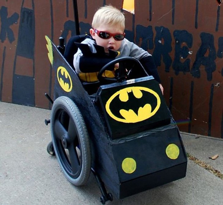 niño en silla de ruedas decorada de batimovil