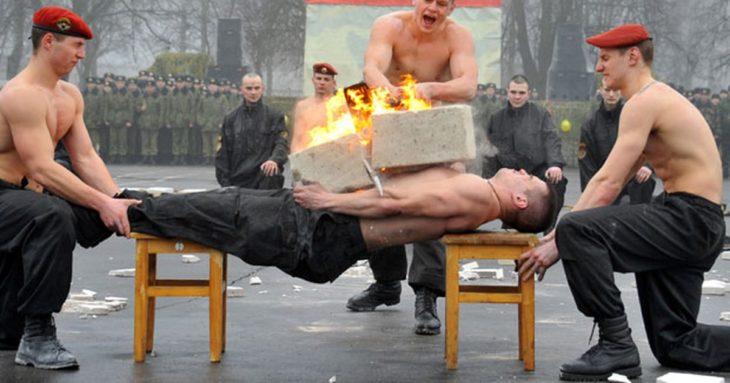 hombres sin camisa, el de enmedio carga un objeto en llamas