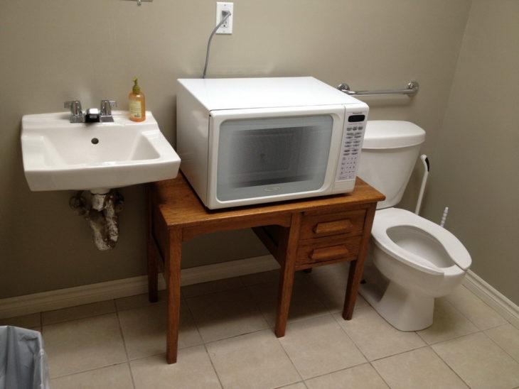 microondas al lado de una tasa de baño