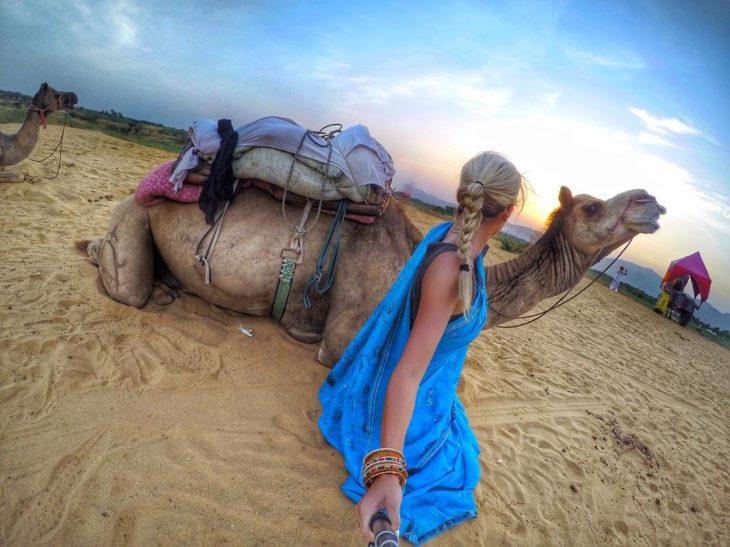 mujer tomándose fotos con un camello