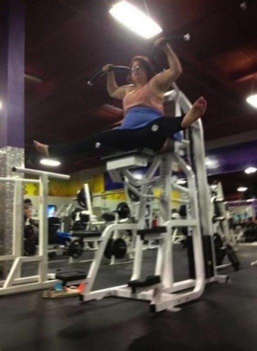 señora utilizando mal aparato de gimnasio
