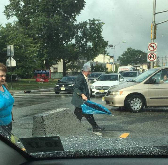 señor con bolsa en la cabeza y paraguas en la mano