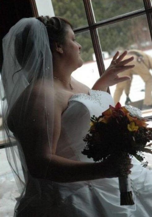 novia mirando a la ventana por fuera el novio está empinado