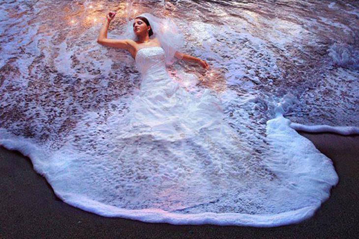 foto de novia con vestido cubierto por una ola