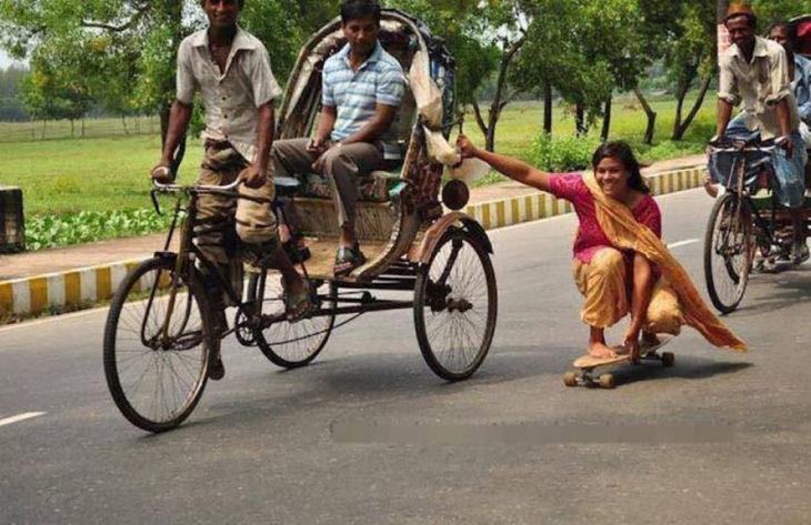 mujer hindú en patineta sostenida de una carreta de bicicletas