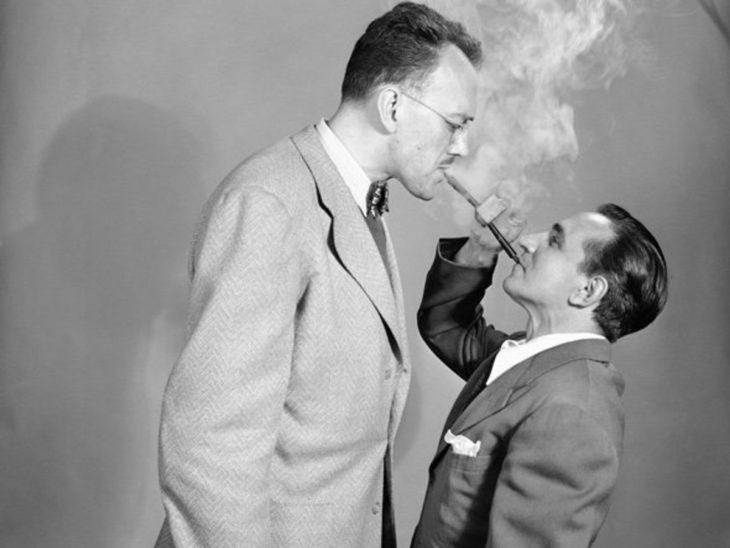 dos hombres fumando una sola pipa