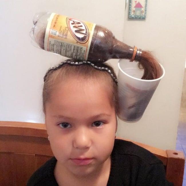 niña con una botella en la cabeza