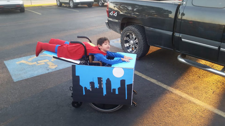 niño disfrazado de superman en silla de ruedas