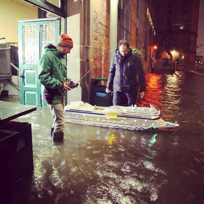 hombres con un barco de motor sobre una inundación