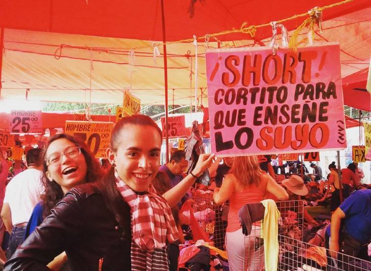 muchachas al lado de cartel