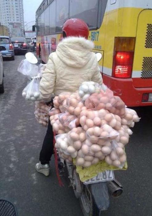 persona transporta huevos en motocicleta
