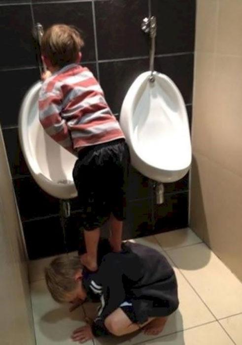 niño hace del baño parado sobre su amigo