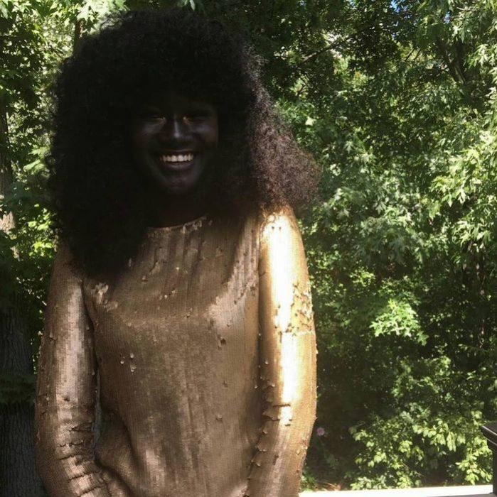 muchacha de vestido dorado y piel oscura