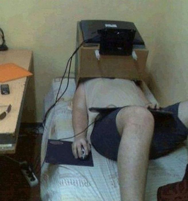 hombre recostado con computadora sobre su cara puesta en una caja