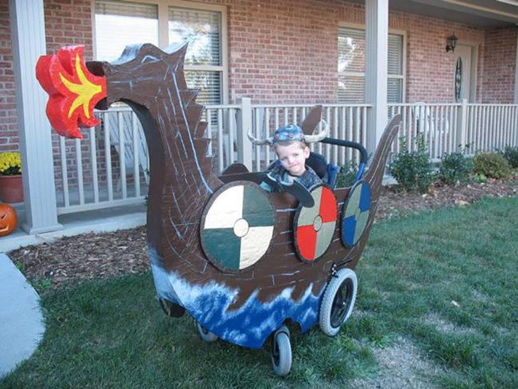 niño en silla de ruedas decorada como barco vikingo