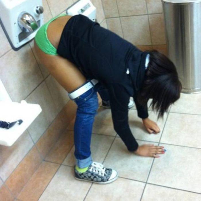 mujer secándose el trasero en el baño