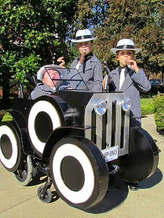 niño disfrazado de gangster en silla de ruedas decorada como auto antiguo