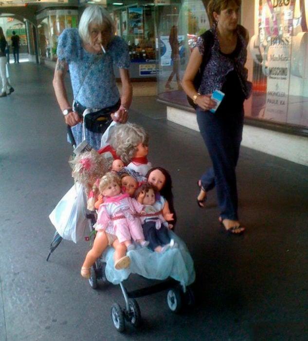 anciano vestido de mujer lleva carreola con muñecas