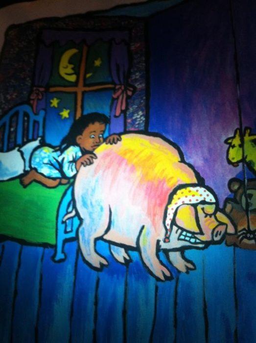 niña viendo el trasero de un cerdo