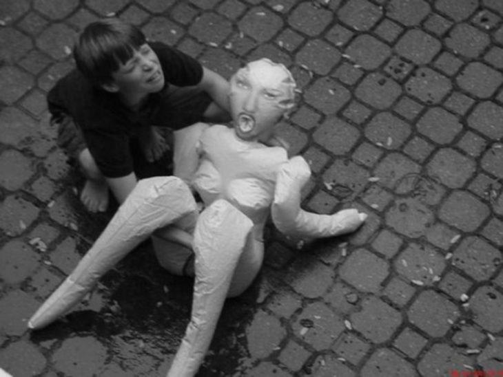 niño con muñeca de plástico en los brazos