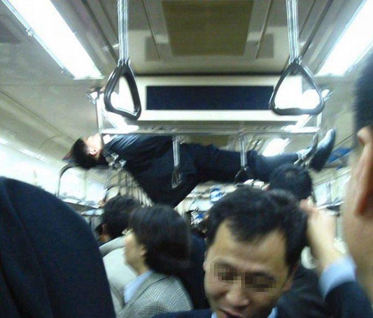 hombre dormido en pasamanos del metro