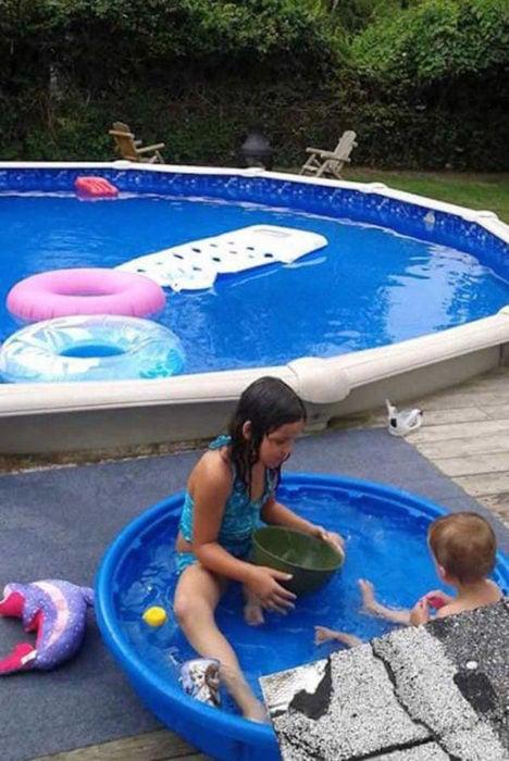 niños en una alberca pequeña mientras hay una piscina grande cerca