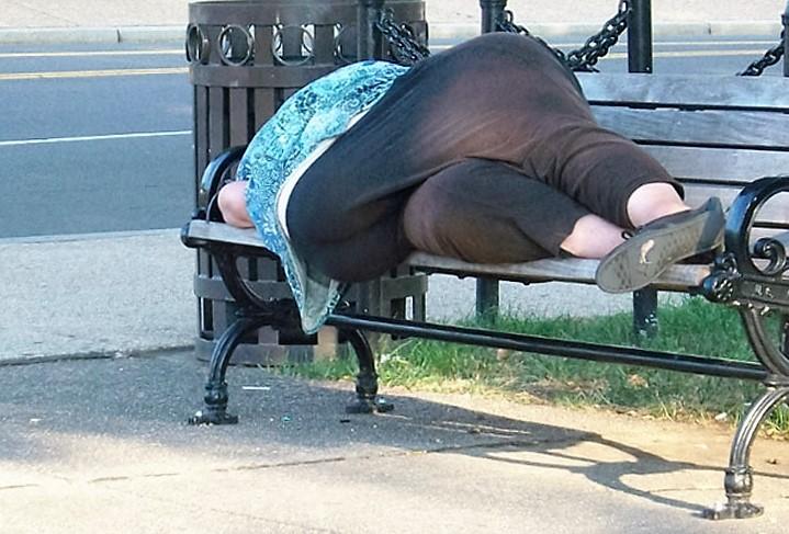 señora acostada en una banca