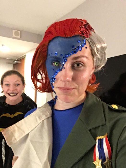 mujer con la mitad de su cara pintada azul y mita de peluca blanca y otra mitad roja