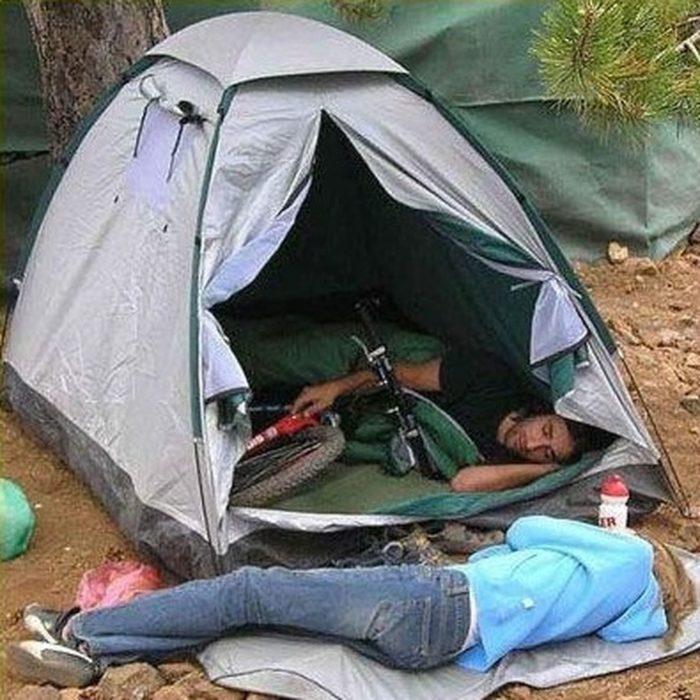 muchacho en casa de campaña abrazando su bicicleta mientras una chica duerme a la interperie