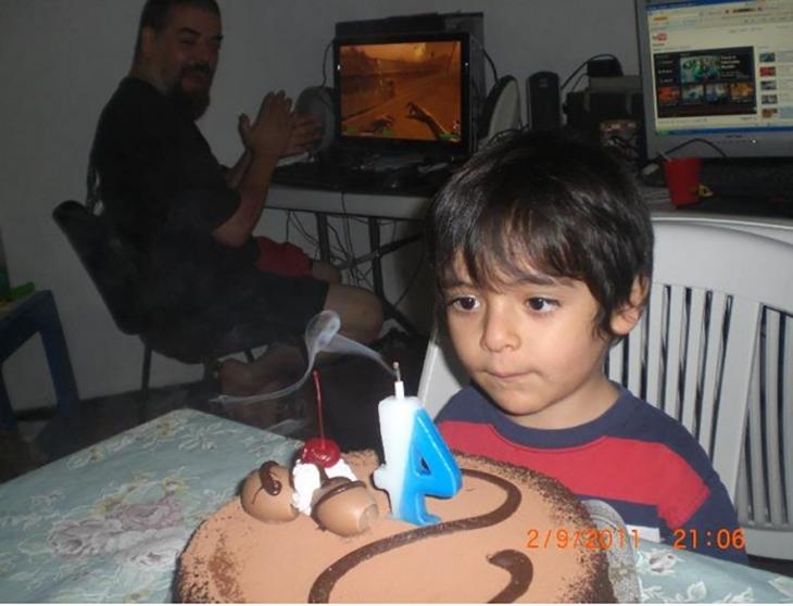 niño soplando la vela de su pastel