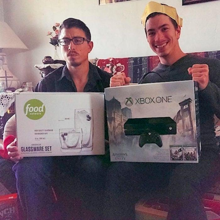 dos jóvenes sosteniendo regalos, uno es un xbox y otro un juego de vasos