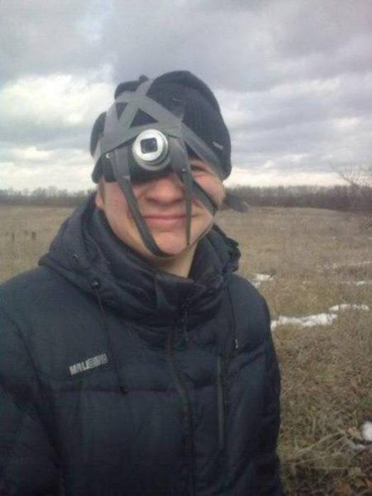 muchacho con cámara pegada con cinta a su sombrero