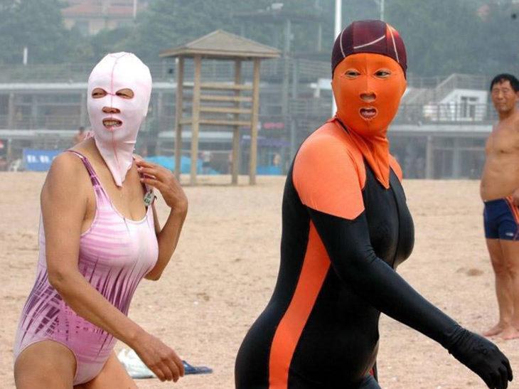 asiaticas en traje de baño con máscaras en la cara